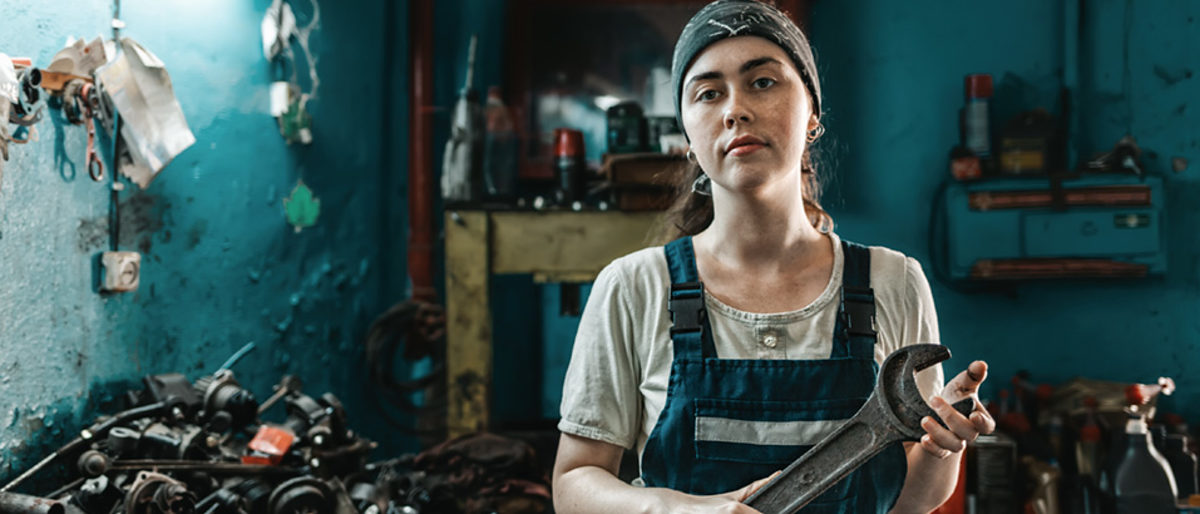 The concept of small business, feminism and women's equality. A young woman in overalls poses with a large wrench in her hands. Schlagwort(e): woman, auto, mechanic, wrench, garage, feminism, business, service, work, factory, technician, car, profession, equality, engine, spare parts, diagnostic, worker, industry, auto repair shop, hobby, occupation, tool, employment, workshop, holding, female, automotive, concept, engineer, mechanical, protection, lifestyle, technique, young, equipment, inspection, transportation, transport, success, safety, apprentice, shop, diy, electronic, vehicle, job, land vehicle, robe, indoors